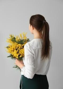 Giovane donna che tiene un mazzo di bellissimi fiori di mimosa su sfondo chiaro