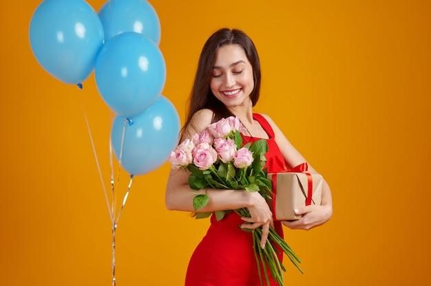 Giovane donna che tiene mazzo di rose e confezione regalo, sfondo giallo. la persona di sesso femminile ha ricevuto una sorpresa, un evento o una festa di compleanno