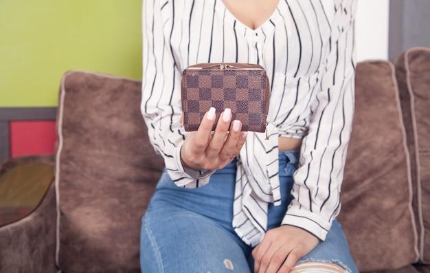 Giovane donna che tiene portafoglio marrone a casa.