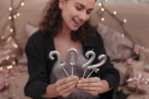 Giovane donna che tiene le candele sotto forma di numeri 2022, concetto di celebrazione del nuovo anno.