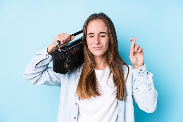 Giovane donna che tiene un cassete isolato dita incrociate per avere fortuna
