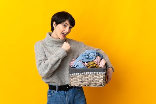 Giovane donna che tiene un cestino dei vestiti che celebra una vittoria