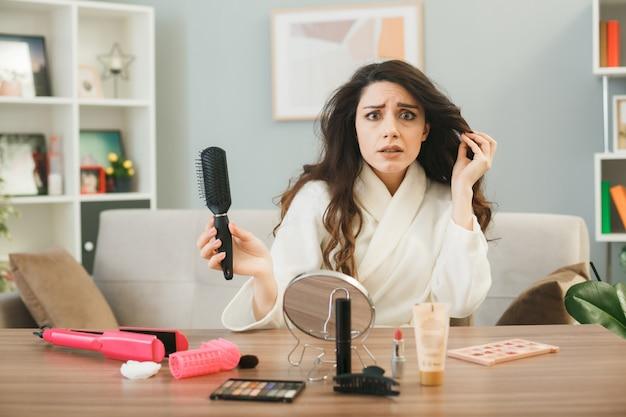 Giovane donna che tiene il pettine seduto al tavolo con strumenti per il trucco in soggiorno