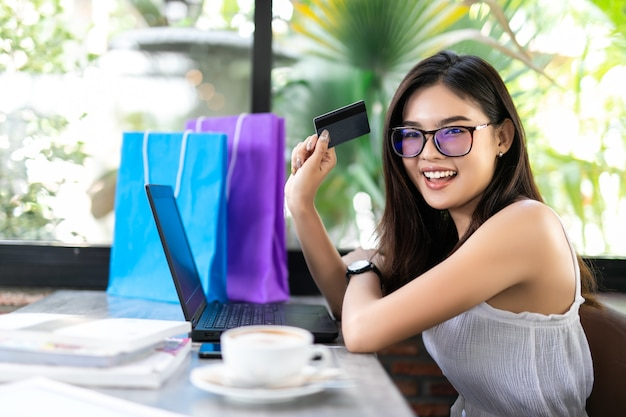 Carta di credito della tenuta della giovane donna e computer portatile usando. concetto di acquisto online