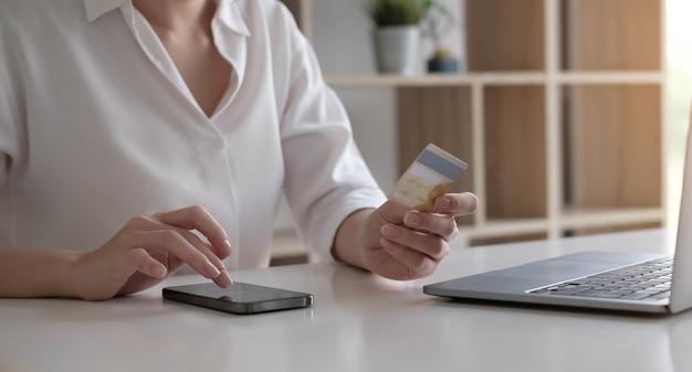 Giovane donna in possesso di carta di credito e utilizzo di computer portatile e smartphone. concetto di acquisto online