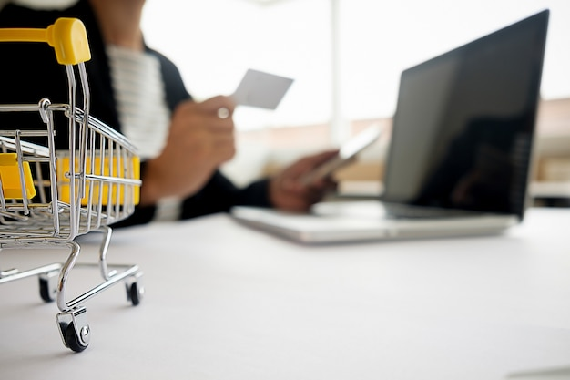 Carta di credito della tenuta della giovane donna e computer portatile usando