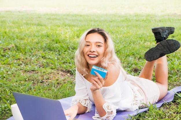Giovane donna in possesso di una carta di credito e che utilizza un computer portatile con il concetto di shopping online