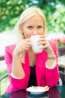 Giovane donna che tiene tazza di caffè