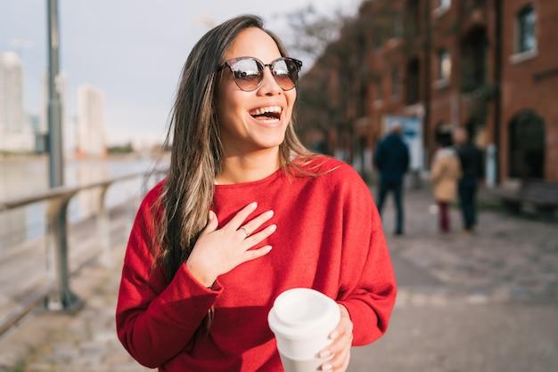 Giovane donna che tiene una tazza di caffè.