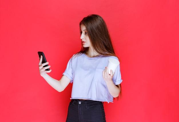 Giovane donna che tiene una tazza di bevanda e controllando i suoi messaggi.