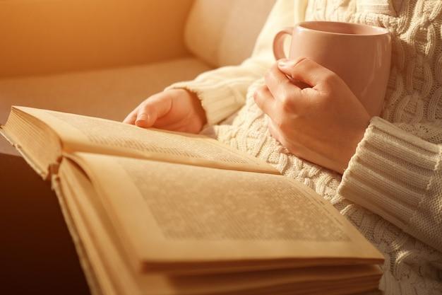 Giovane donna che tiene una tazza di tè e legge un libro aperto, luce solare