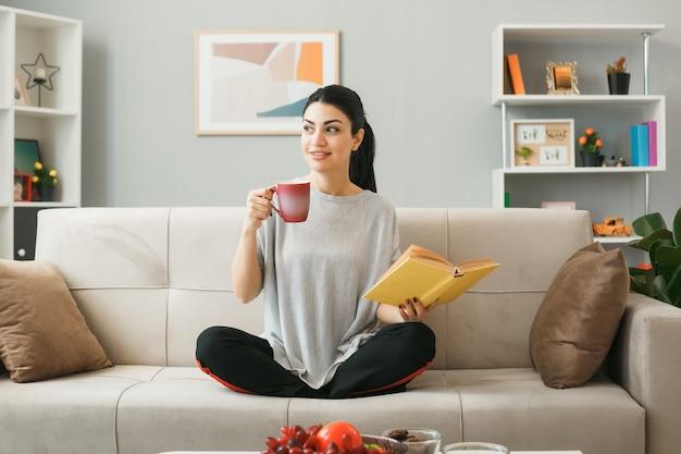 Giovane donna che tiene tazza di tè con libro seduto sul divano dietro il tavolino da caffè in soggiorno