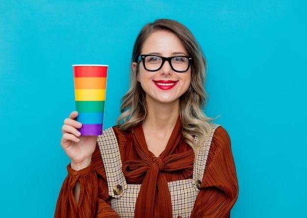 Giovane donna che tiene una tazza con i colori dell'arcobaleno sull'azzurro