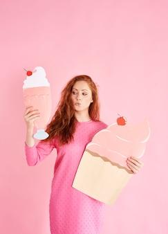 Giovane donna che tiene un cupcake e un frullato allo studio shot