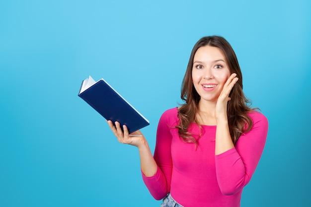 Giovane donna che tiene un diario o un libro e tocca il viso con la mano