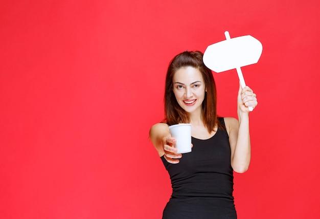 Giovane donna che tiene una tazza di bevanda usa e getta e un banco informazioni bianco e offre la bevanda al cliente