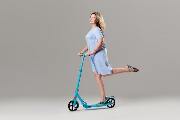 Giovane donna che tiene lo scooter elettrico e guidarlo mentre si sente felice. ritratto integrale di una ragazza estatica che guida un motorino sulla parete bianca
