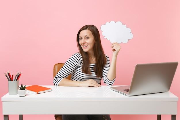 Giovane donna in possesso di vuoto vuoto say cloud nuvoletta sedersi e lavorare alla scrivania bianca con pc portatile isolato su sfondo rosa pastello. concetto di carriera aziendale di successo. copia spazio per la pubblicità.