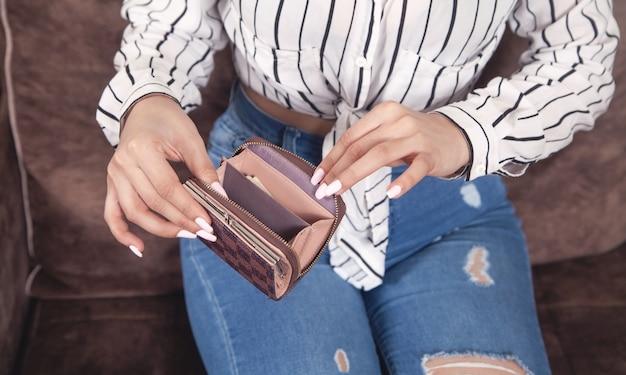 Giovane donna che tiene portafoglio marrone vuoto a casa.