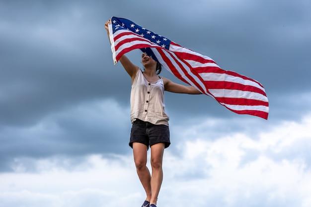 Giovane donna che tiene la bandiera dell'america sullo sfondo del cielo.