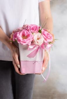 Giovane donna che tiene un contenitore di fiore con le rose e le eustomas rosa delicate