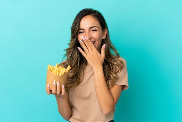 Giovane donna che tiene patatine fritte su sfondo isolato felice e sorridente che copre la bocca con la mano