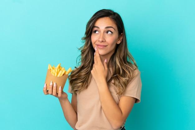 Giovane donna che tiene patatine fritte su sfondo isolato guardando in alto mentre sorride