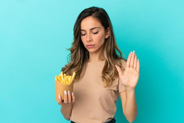 Giovane donna che tiene patatine fritte su sfondo isolato facendo gesto di arresto e deluso