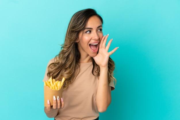 Giovane donna che tiene patatine fritte su sfondo isolato che grida con la bocca spalancata di lato