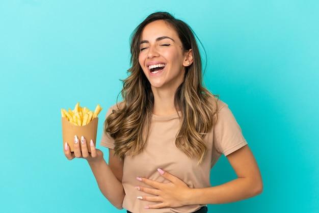 Giovane donna che tiene patatine fritte su sfondo isolato sorridendo molto
