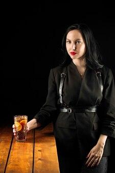 Giovane donna che tiene un bicchiere di cocktail di tè freddo long island fresco