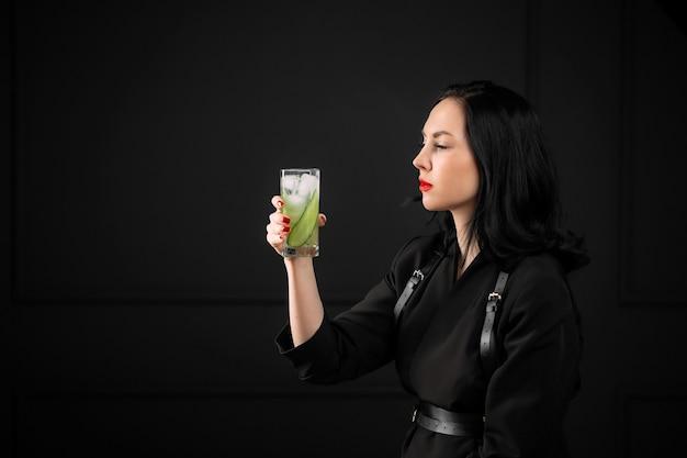 Giovane donna con in mano un bicchiere di gin tonic cocktail