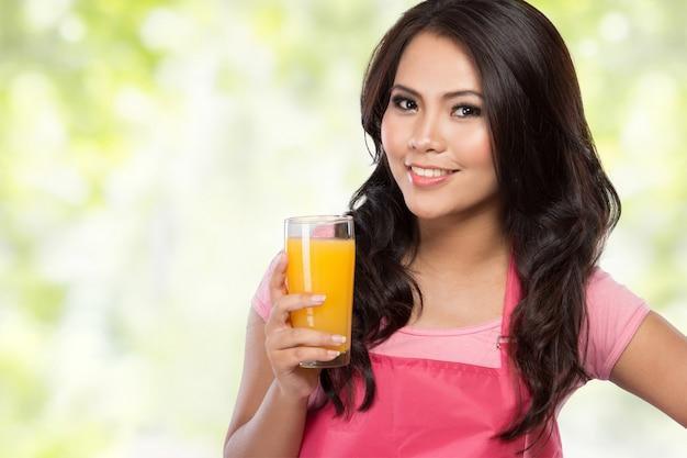 Giovane donna che tiene vetro di succo d'arancia