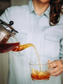 Giovane donna che tiene una teiera di vetro. donna versando il tè