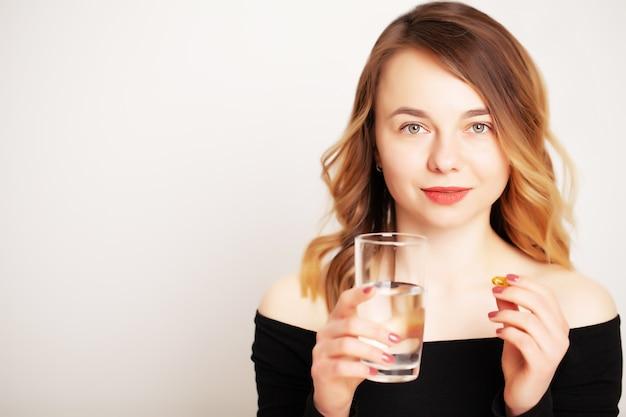 Giovane donna che tiene un bicchiere d'acqua e una pillola per perdita di peso
