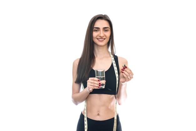 Giovane donna con in mano un bicchiere d'acqua e una pillola