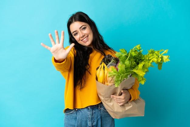 Giovane donna che tiene un sacchetto della spesa della drogheria sull'azzurro che conta cinque con le dita