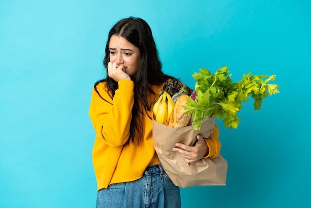 Giovane donna che tiene un sacchetto della spesa isolato