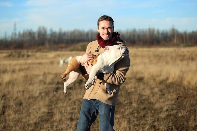 Giovane donna che tiene in mano un cane di razza bulldog inglese in autunno soleggiato campo