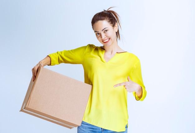 Giovane donna che tiene il suo pacco di cartone e lo introduce