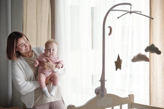 Giovane donna che tiene in braccio la sua graziosa bambina e la guarda