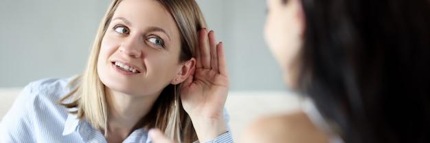 Giovane donna che tiene il suo orecchio e parlando con un amico. concetto di ipoacusia congenita e acquisita
