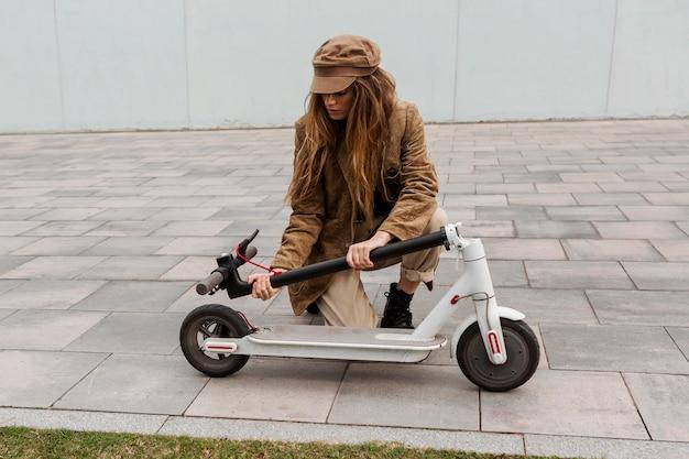 Giovane donna che tiene il suo scooter elettrico