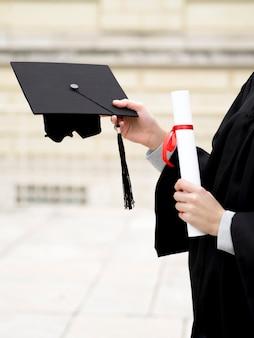 Giovane donna che tiene il suo cappello di laurea