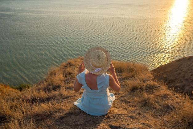 Giovane donna che tiene il suo cappello con nastro bianco con le mani attraverso il vento sulle rive al tramonto.