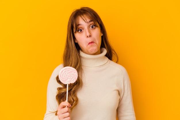 Giovane donna che tiene un lecca-lecca isolato sul muro giallo alza le spalle e apre gli occhi confusi