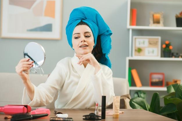 Giovane donna che tiene e guarda lo specchio avvolto i capelli in un asciugamano seduto al tavolo con strumenti per il trucco in soggiorno