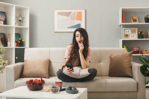 Giovane donna che tiene in mano e guarda il telefono morde un biscotto seduto sul divano dietro il tavolino da caffè nel soggiorno