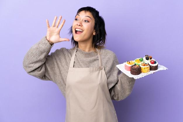 Giovane donna che tiene i lotti di mini torte differenti sopra spazio viola isolato che grida con la bocca spalancata