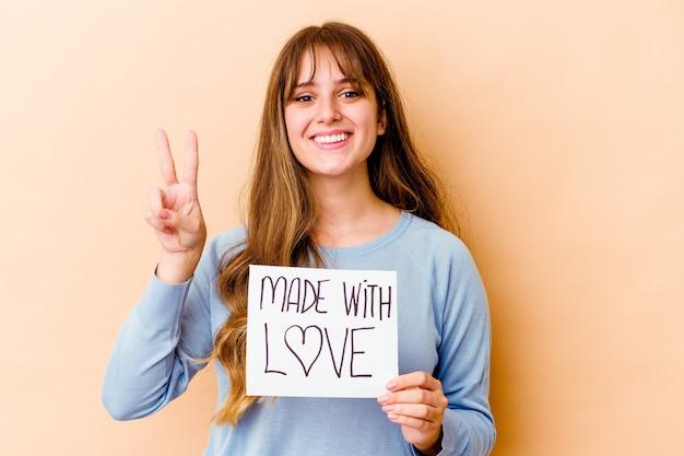 Giovane donna che tiene un fatto con amore cartello isolato che mostra il numero due con le dita